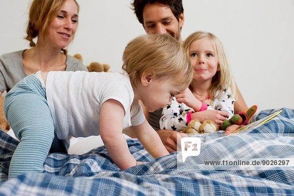 Ein Jahr altes Mädchen krabbelt auf dem Bett der Eltern