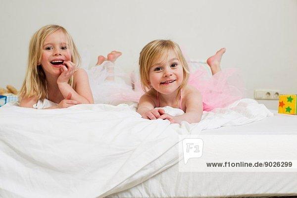 Porträt zweier junger Schwestern auf dem Bett liegend Porträt zweier junger Schwestern auf dem Bett liegend