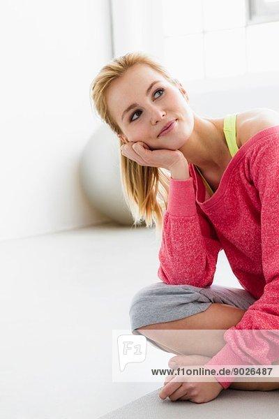Junge Frau auf Trainingsmatte sitzend