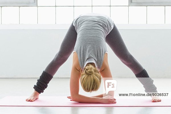 Young woman in yoga pose  bending forwards