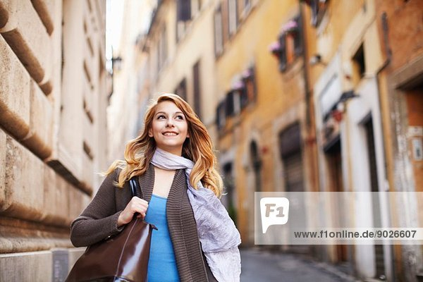 Young woman strolling down street  Rome  Italy