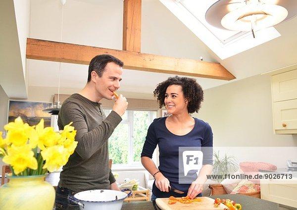 Paar in der Küche schmecken und Paprika schneiden