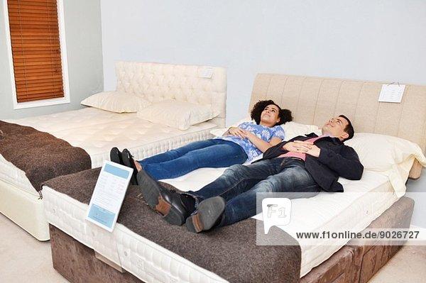 Paar auf dem Bett liegend im Möbelhaus-Showroom