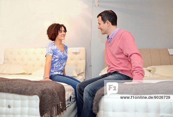 Paar auf Betten sitzend im Ausstellungsraum des Möbelhauses