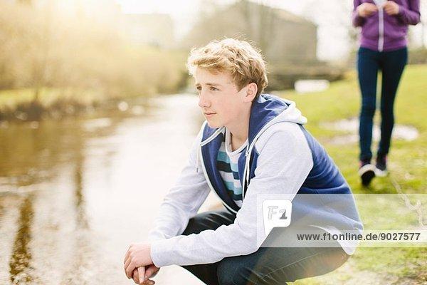 Unhappy teenage boy crouching on riverbank