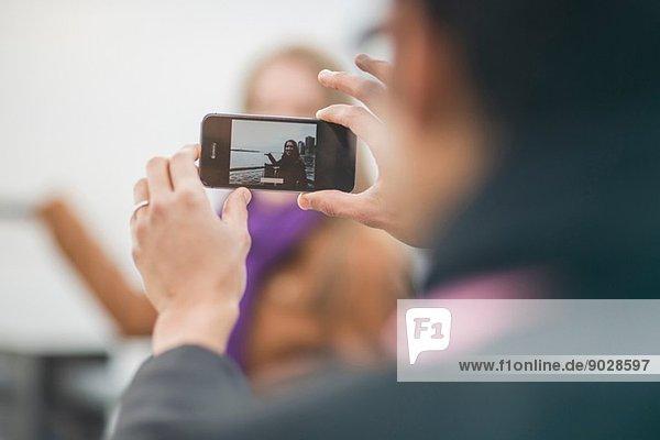 Nahaufnahme eines jungen Mannes  der seine Freundin fotografiert.