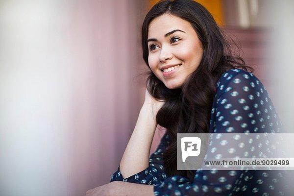 Junge Frau lächelnd und wegschauend