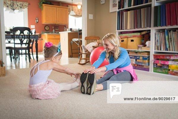 Mutter und Tochter beim Aufwärmen für Ballett im Wohnzimmer