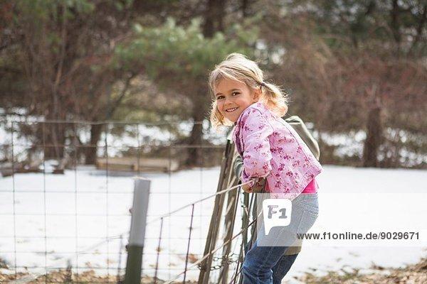 Junges Mädchen klettert auf Drahtzaun im Feld
