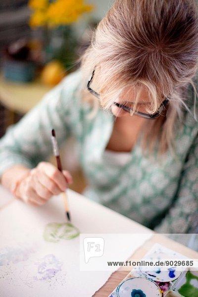 Nahaufnahme der reifen Künstlerin Aquarellmalerei im Atelier