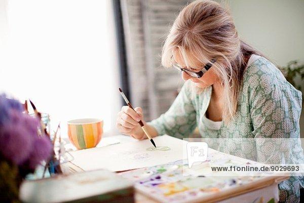 Reife Künstlerin Aquarellmalerei im Atelier