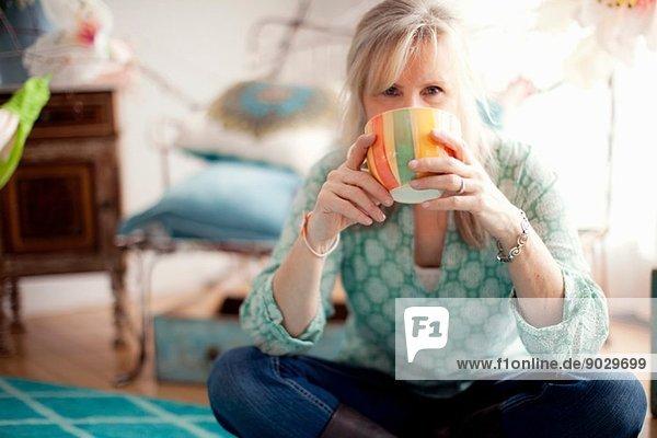 Reife Frau sitzt im Schneidersitz und trinkt Kaffee.