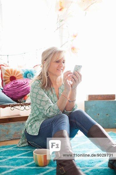 Reife Frau auf dem Boden sitzend SMS auf dem Handy