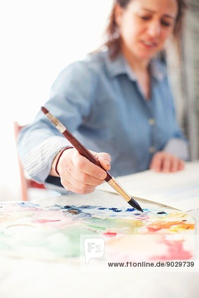 Reife Künstlerin beim Aquarellieren im Atelier