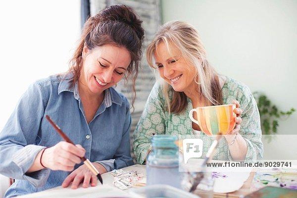 Zwei reife Künstlerinnen malen im Atelier