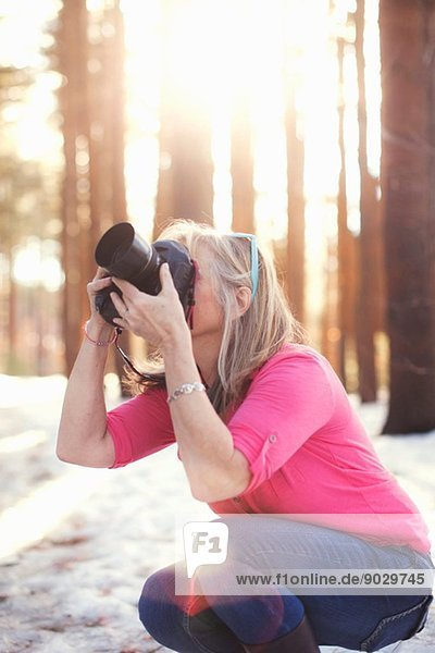 Reife Frau beim Fotografieren im Wald