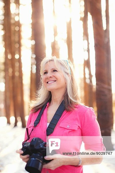 Mature female photographer in forest