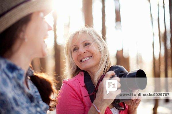 Zwei reife Frauen mit Digitalkamera im Wald
