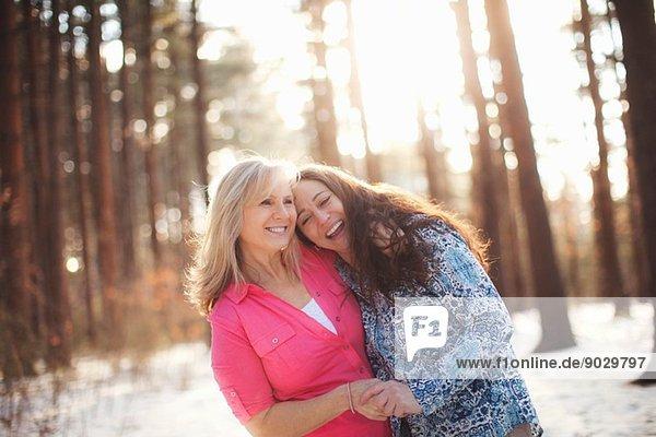 Porträt von reifen Frauen  die sich im Wald umarmen