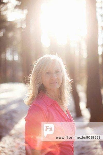 Porträt einer reifen Frau im sonnigen Wald