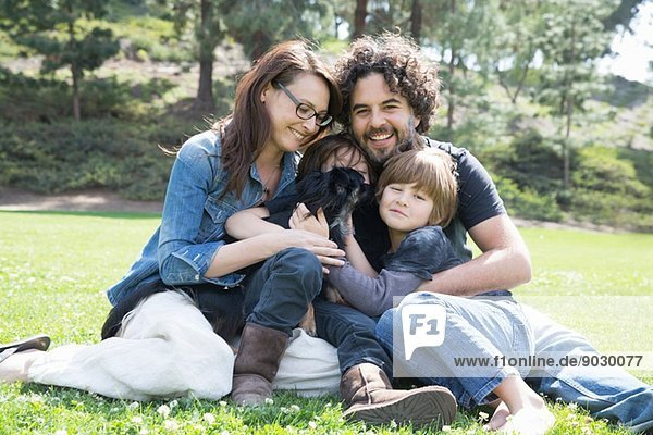 Portrait of family with two boys and dog sitting in park