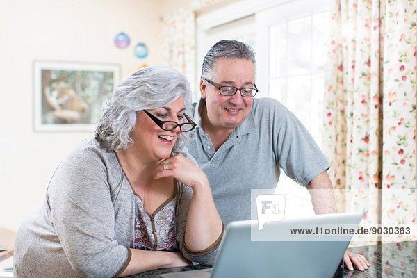 Reife Paare zu Hause mit dem Laptop