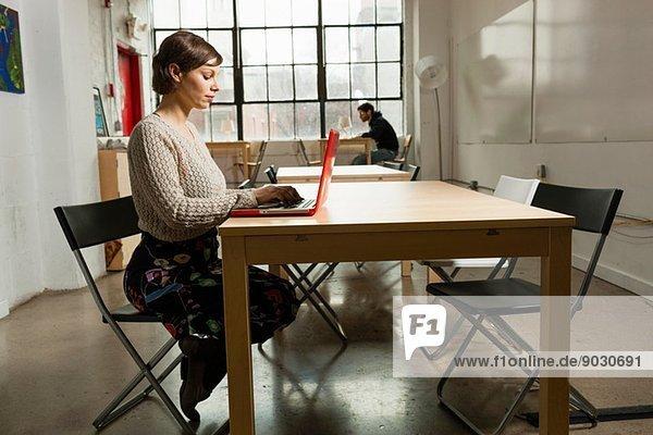 Junge Designerin beschäftigt am Laptop im Designstudio