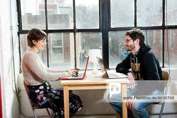 Designerinnen und Designer bei der Arbeit an Laptops im Studio