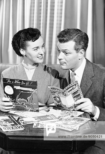 Couple with brochures deciding on vacation