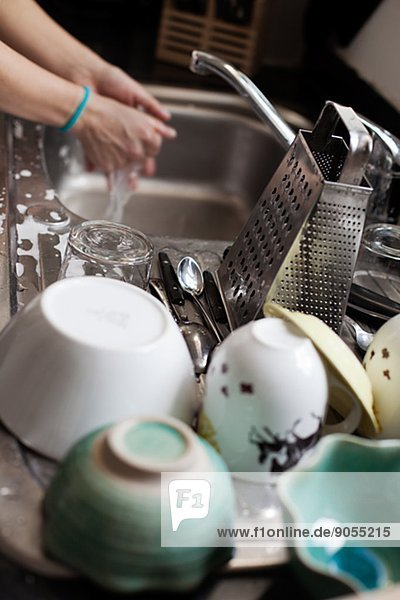 Woman washing dishes  cups on foreground