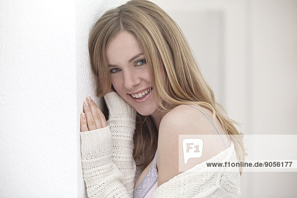 Lächelnde Frau lehnt an einer Wand  Porträt