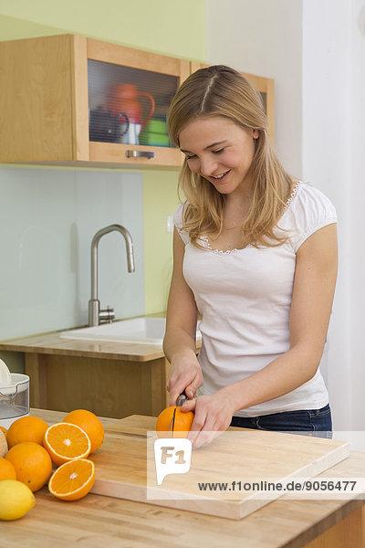 Junge Frau schneidet Apfelsinen in der Küche