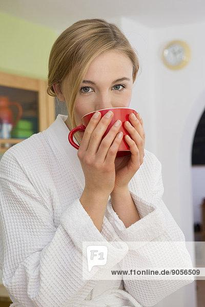 Junge Frau im Bademantel hält einen Kaffeebecher