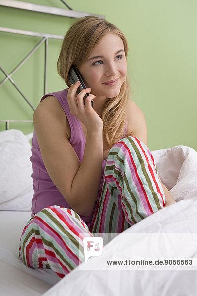 Junge Frau telefoniert im Bett