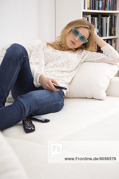 Junge Frau auf der Couch schaut fernsehen