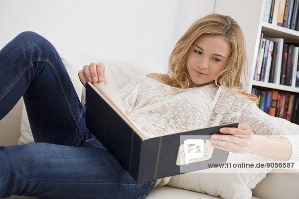 Junge Frau schaut in ein Fotoalbum