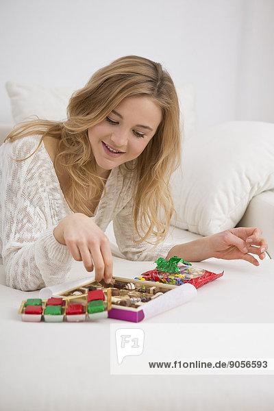 Junge Frau auf der Couch nascht Süßigkeiten