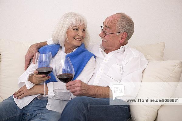 Seniorenpaar auf der Couch trinkt Rotwein