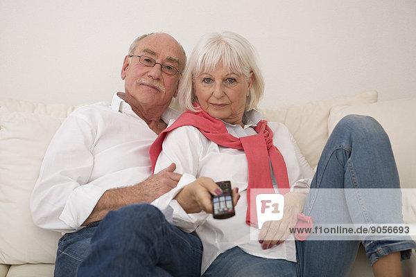 Seniorenpaar auf der Couch schaut fernsehen