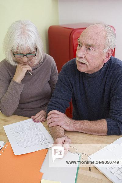 Seniorenpaar liest ein Dokument am Tisch