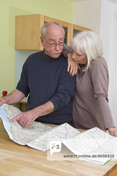 Seniorenpaar schaut auf eine Landkarte