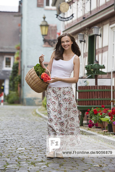Smiling woman carrying basket with flowers