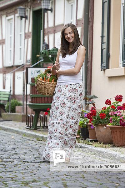Lächelnde Frau trägt einen Korb mit Gemüse