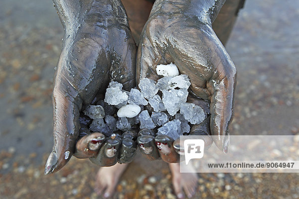 Woman's hands holding salt crystals  hands covered in salty mud from the Dead Sea  Suwayma  Jordan
