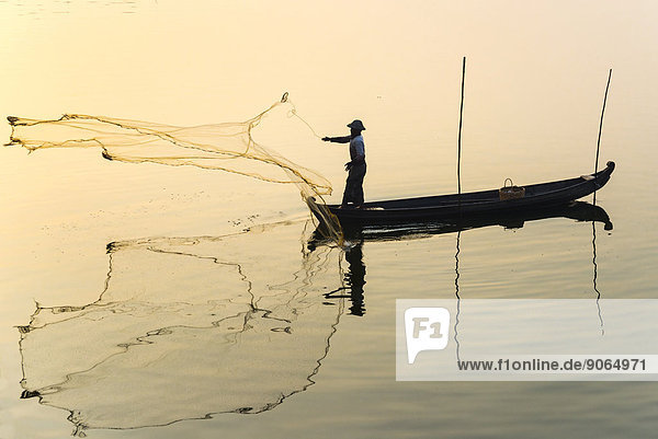 Fisherman in a boat tossing out a net  morning light  Thaungthaman Lake  Amarapura  Mandalay Division  Myanmar