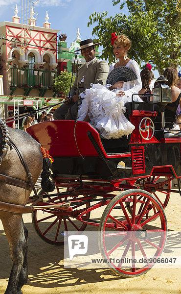 Kutscher in Uniform und junge Frau in einem Flamencokleid auf der Pferdemesse Feria del Caballo  Jerez de la Frontera  Provinz Cádiz  Andalusien  Spanien