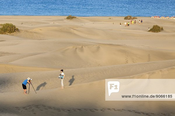 Spain,  Canary Islands,  Gran Canaria,  Photographer with model in sand dunes of Maspalomas