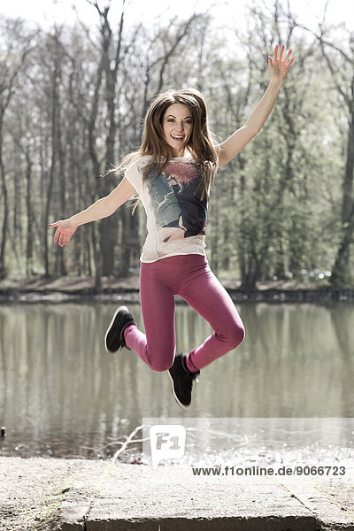 Woman jumping in the air in front of water