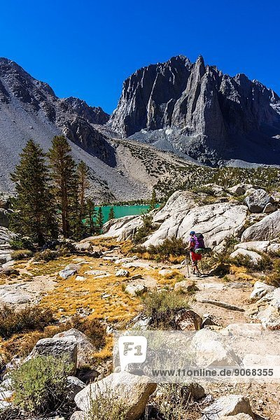 Backpacker at Second Lake under Temple Crag and the Palisades  John Muir Wilderness  California USA.