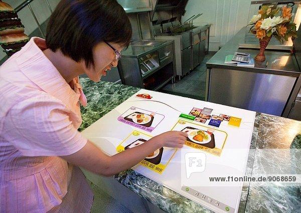 Young Woman Looking At Menu In A Hamburger Restaurant  Pyongyang  North Korea.